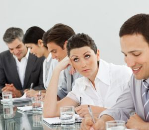 A photo of a woman sitting at a table rolling her eyes at her employees instead of working with them.